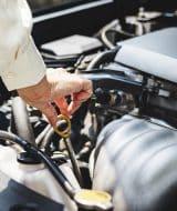 Hombre cambiando el aceite del motor a su coche