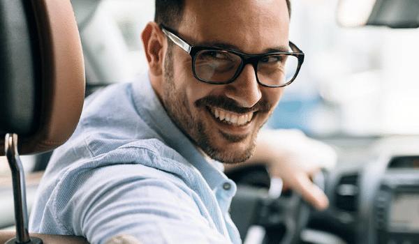 Hombre feliz sonriendo en su coche mejorado